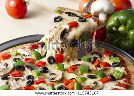 Image of a melted pizza on a stainless pan over the wooden table - stock photo