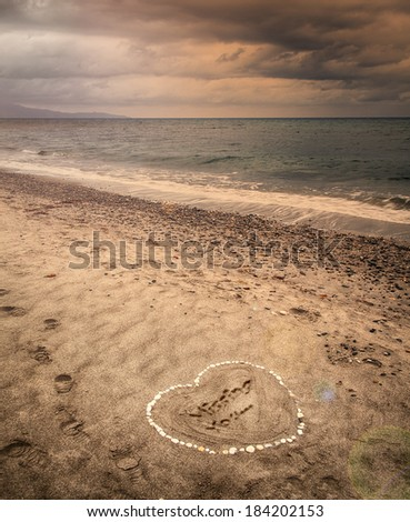 Image of a message of missing love written in sand on a stormy beach.  - stock photo