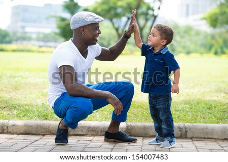 Image of a modern father giving a hi-five his little son in the park - stock photo