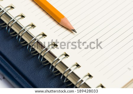 image of a notebooks and pencil on the desk, close-up - stock photo