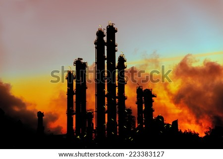 Image of a power plant in the early hours at dawn with a fiery orange sky and smoke fumes being pumped into the atmosphere - stock photo