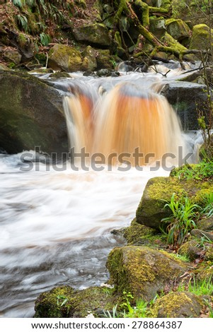 Image of a running river through moss covered rocks in a gorge - stock photo