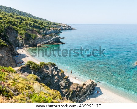 Image of a secluded bay on the island of Skopelos, Greece with clear blue and green waters and sandy beaches. An image of peace, calm and tranquility associated with relaxing summer holidays.  - stock photo