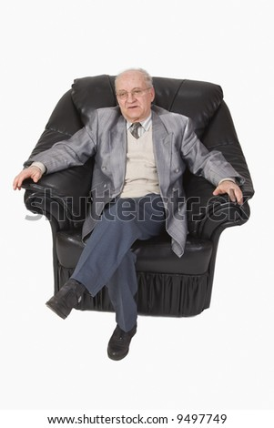 Image of a senior speaking while he is sitting relaxed in an armchair-upper view. - stock photo