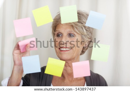 Image of a senior woman removing sticky notes. - stock photo