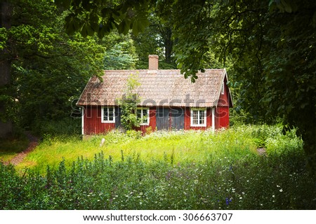 Image of a small red cottage in a forrest clearing. South east Sweden.  - stock photo