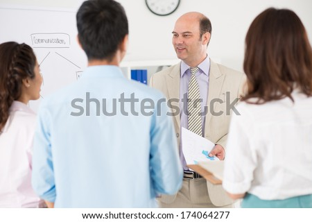 Image of a smiley boss with documents in hands standing and talking with his partners after business conference on the foreground  - stock photo