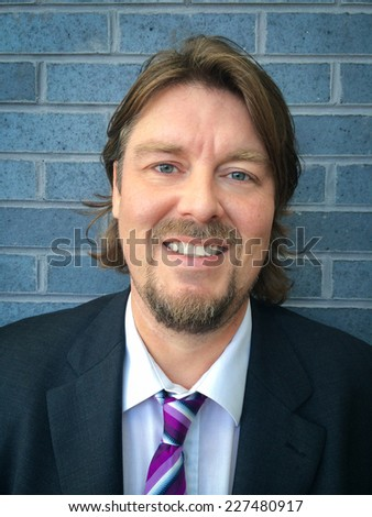 Image of a smiling business man in suit leaning against a wall - stock photo