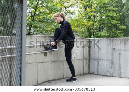 Image of a sporty female tying shoelaces during training - stock photo
