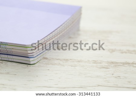 Image of a stack of colorful notebooks on a white wooden table.  - stock photo