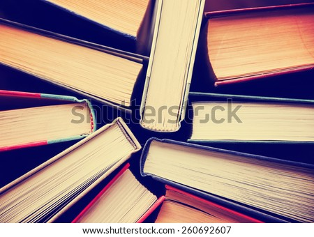 image of a stack of hard back books on the end of the pages toned with a retro vintage warm instagram like filter app or action effect - stock photo