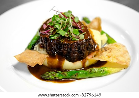 Image of a steak fillet on a bed of mashed potatoes with asparagus, chips and gravy - stock photo