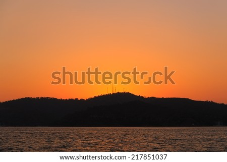 Image of a sunset over the sea with mountains and communication mast silhouetted far in the distance - stock photo