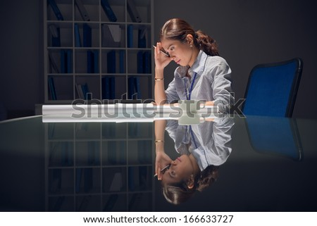 Image of a tired businesswoman working alone before deadline at the office in the night - stock photo