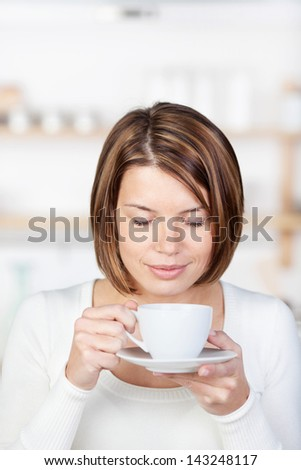 Image of a woman drinking coffee with closed eyes, standing in the kitchen. - stock photo