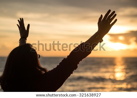 Image of a woman raising hands in freedom against beautiful sunset sky background  - stock photo