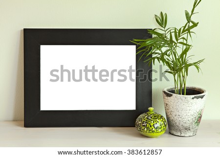 Image of a wooden frame mockup scene, on green wall.  - stock photo