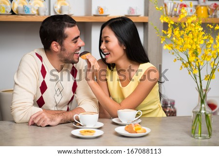 Image of a young adorable couple at a coffee shop, a girlfriend feeding her boyfriend with a tasty chocolate snack  - stock photo