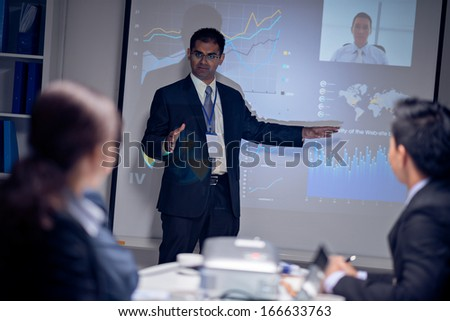 Image of a young Asian businessman explaining the company's activity at the presentation while his colleague is online on the foreground  - stock photo