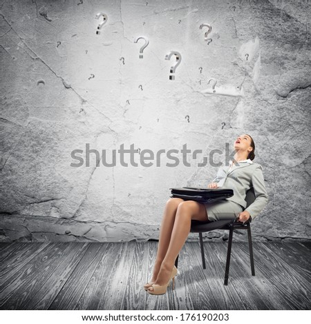 image of a young business woman looking at the question marks - stock photo