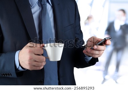 Image of a  young businessmen standing in  the office and holding the mobile phone - stock photo