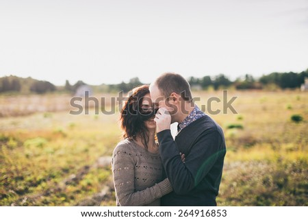 Image of a young couple enjoying their time together at countryside. Man is playing with woman's curly hair. - stock photo