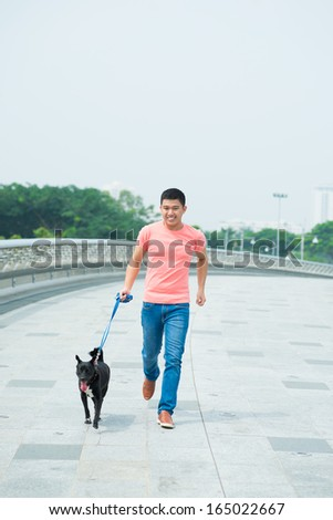 Image of a young man walking with his dog outside - stock photo