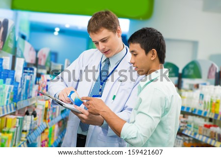Image of a young medical intern helping the client to choose the treatment on the foreground - stock photo