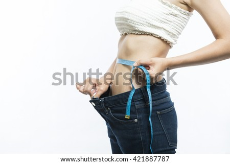 Image of a young slim woman using a measuring tape on her waist - stock photo