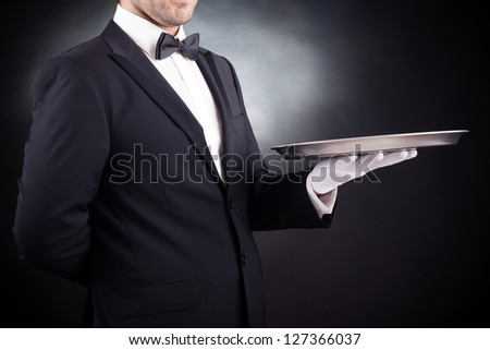 Image of a young waiter holding an empty dish on black background - stock photo