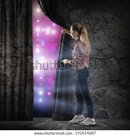 image of a young woman, changes reality, looking at the lights of a stone wall - stock photo