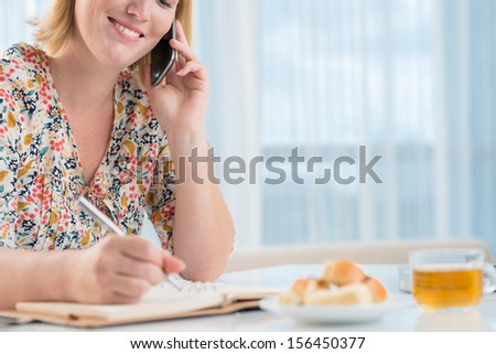 Image of a young woman talking by phone and making notes on the week-end on the foreground - stock photo
