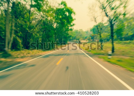 Image of Abstract blur road with motion on day time for background usage . (vintage tone) - stock photo