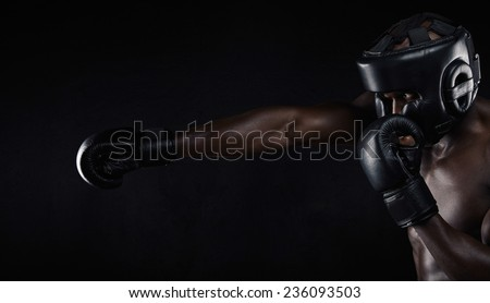 Image of african male boxer boxing against black background. Young man wearing protective head guard and boxing gloves practicing for fight. - stock photo