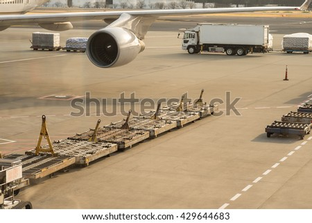 Image of aircraft wing at luggage loading area at the airport terminal with selective focused point for transportation background - stock photo