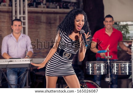 Image of an adorable singer performing emotionally on the stage with the music band on the foreground - stock photo