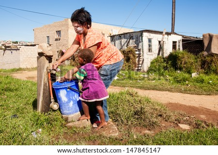 image of an african mother cleaning her daughters hands under running water in the township - stock photo