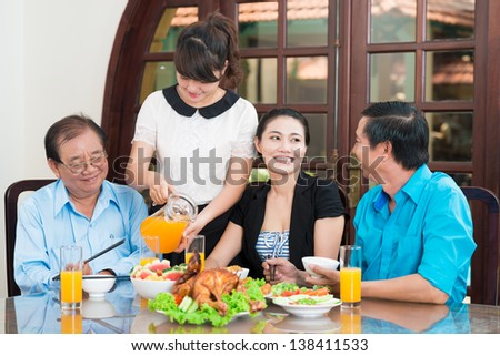 Image of an Asian family sitting at the table together - stock photo