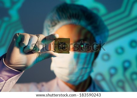 Image of an electronic engineer analyzing computer microchip holding on the foreground  - stock photo