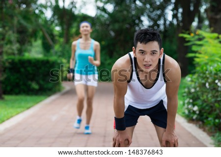 Image of an exhausted sportsman standing on the foreground - stock photo
