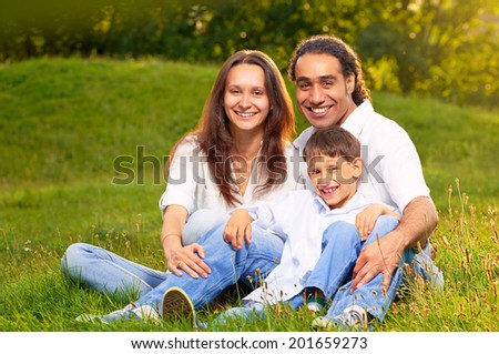 Image of an international family sitting together in the park - stock photo
