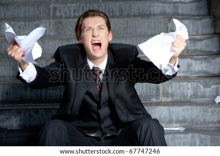 Image of angry businessman with papers in hands raising its - stock photo