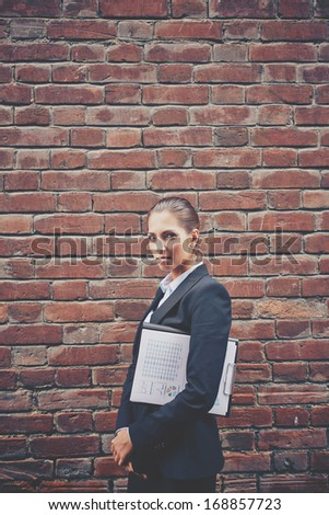 Image of angry businesswoman with document walking along brick wall - stock photo