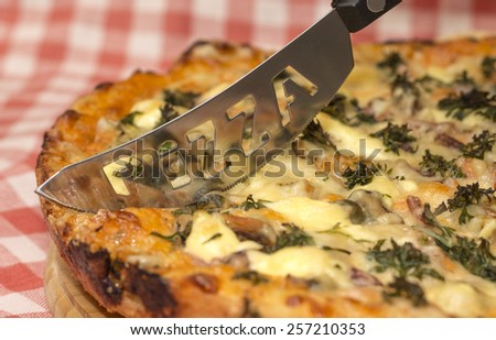 Image of appetizing homemade pizza and original knife - stock photo