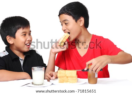 image of asian boys sharing a food - stock photo