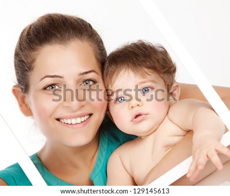 Image of attractive female holding in hands cute baby boy, closeup portrait of young mother hug her little son, white frame decorations, studio shot, happy family, child care and love concept - stock photo