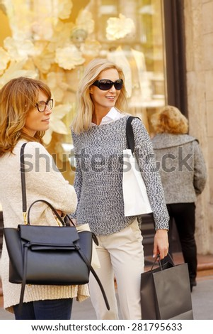 Image of attractive women with shopping bags standing in front of fashion store and talking. - stock photo