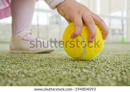 Image of baby catching tennis ball. Learning sport from birth. - stock photo