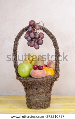 Image of basket with fruits on yellow wooden table. - stock photo