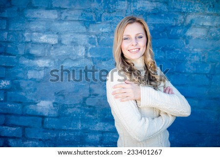 image of beautiful blond young lady in white sweater at blue concrete wall copy space background - stock photo